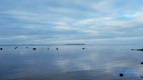 Beautiful seascape, calm sea, blue sky. Reflected in water, island on the horizon stock video