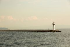 Beautiful seascape with lighthouse. Calm sea and a lighthouse on the pier. Small beacon in the endless sea. Landscape. And beacon. Lighthouse Royalty Free Stock Images