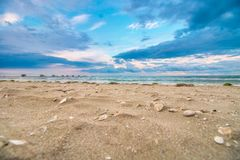Beautiful seascape panorama with waves and seashells on the hot sand royalty free stock photography