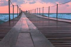 Beautiful seascape with pink sunset, pier and storm waves in evening. Beautiful seascape with pink sunset, pier and storm waves stock image