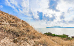 Beautiful seascape with rocks and meadow in cloudy blue sky Royalty Free Stock Image