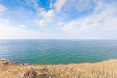 Beautiful seascape with rocks and meadow in cloudy blue sky Stock Photography