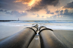Beautiful seascape with soft waves hitting concrete drainage pipe. On the beach over sunrise background and dramatic dark clouds royalty free stock images