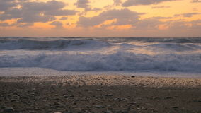 Beautiful seascape at the sunset background. The camera is on the beach. The sky illuminates the sunset. The camera takes off the sea and waves. Waves cover the stock video footage