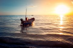 Beautiful seascape view the fishing boat floating on the sea with sunset light in the background. Selective focus Stock Image