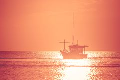 Beautiful seascape view of fishing boat floating on the sea with sunset light in the background. Selective focus Stock Photo