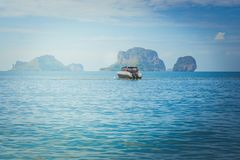 Beautiful seascape view of lonely speed boat floating on the sea with island and blue sky in the background at Railay Beach. stock illustration