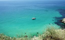 Beautiful seascape with a yacht, blue transparent water and white sand royalty free stock images