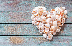 Beautiful seashell heart on rustic wood. Beautiful seashell heart formed of multiple small bivalves, cones and conches on rustic weathered wooden boards with Royalty Free Stock Photography
