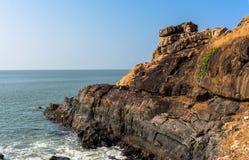 Beautiful seashore with sea wave over rocks. Turquoise clean seawater. White wavy foam of sea surf. Gokarna, India Royalty Free Stock Photo
