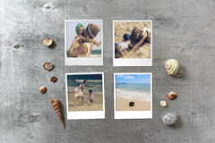 Beautiful seaside snapshots arranged on rustic wooden background with seashells around Stock Image
