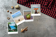 Beautiful seaside snapshots arranged on rustic wooden background with seashells around Stock Image