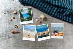 Beautiful seaside snapshots arranged on rustic wooden background with seashells around Stock Photos