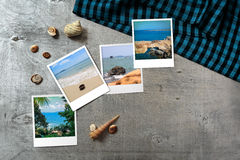 Beautiful seaside snapshots arranged on rustic wooden background with seashells around Stock Photo