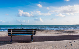 Beautiful seaside view, sandy beach, bench, blue sky, ocean and Stock Image