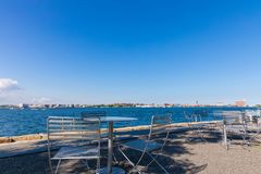 Tables and chairs on Sunny day at Fan Pier Park Boston, Massachusetts. Close to sea stock photography