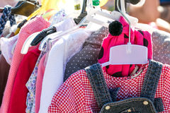 Beautiful second hand girl clothes at garage sale to reuse. Close-up of beautiful second hand baby girl and child clothes displayed at outdoor garage sale for Stock Photography