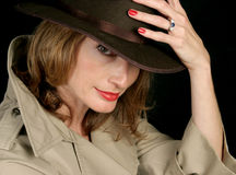 Beautiful Secret Agent. A beautiful woman dressed as a secret agent in a trenchcoat and fedora hat Stock Photography