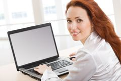 Beautiful secretary. Portrait of beautiful secretary while typing on the laptop Royalty Free Stock Photography