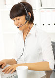 Beautiful secretary with headset. Is working in office Stock Photos