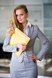 Beautiful secretary in the office. Standing with a folder Stock Photography