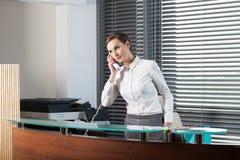 Beautiful secretary at office. Beautiful secretary talking on the phone at office Stock Image