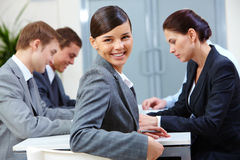 Beautiful secretary. Portrait of beautiful secretary looking at camera on the background of co-workers royalty free stock image