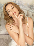Beautiful Secretive Young Woman Posing on a Bed Royalty Free Stock Photo