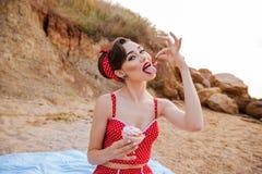 Beautiful seductive pin up girl eating cream cake Royalty Free Stock Photo