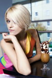 Beautiful seductive woman at a counter in a cafe. Beautiful modern trendy seductive young blond woman sitting at a counter in a coffee house looking sideways at royalty free stock photos