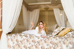 Beautiful seductive woman flirting with the camera lying on the bed with in White bathrobe looking up with a coquettish Stock Images