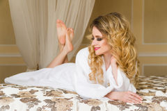Beautiful seductive woman flirting with the camera lying on the bed with in White bathrobe looking up with a coquettish Stock Photo