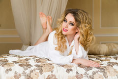 Beautiful seductive woman flirting with the camera lying on the bed with in White bathrobe looking up with a coquettish Stock Photos