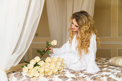 Beautiful seductive woman flirting with the camera is sitting on the bed with a big bouquet of white roses in White Royalty Free Stock Image