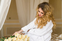 Beautiful seductive woman flirting with the camera is sitting on the bed with a big bouquet of white roses in White Stock Photo