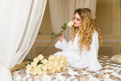 Beautiful seductive woman flirting with the camera is sitting on the bed with a big bouquet of white roses in White Royalty Free Stock Photography