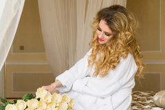 Beautiful seductive woman flirting with the camera is sitting on the bed with a big bouquet of white roses in White Stock Photography