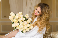Beautiful seductive woman flirting with the camera is sitting on the bed with a big bouquet of white roses in White Royalty Free Stock Images