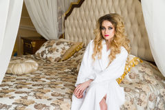 Beautiful seductive woman flirting with the camera sitting on a bed in White bathrobe looking up with a coquettish look Stock Image