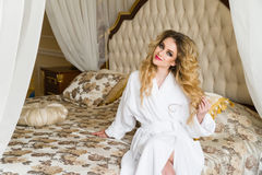 Beautiful seductive woman flirting with the camera sitting on a bed in White bathrobe looking up with a coquettish look Stock Images