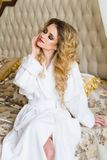 Beautiful seductive woman flirting with the camera sitting on a bed in White bathrobe looking up with a coquettish look Royalty Free Stock Images