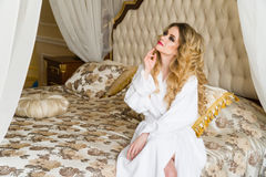 Beautiful seductive woman flirting with the camera sitting on a bed in White bathrobe looking up with a coquettish look Stock Photos