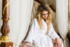 Beautiful seductive woman flirting with the camera sitting on a bed in White bathrobe looking up with a coquettish look Royalty Free Stock Photography
