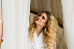 Beautiful seductive woman flirting with the camera sitting on a bed in White bathrobe looking up with a coquettish look Royalty Free Stock Photo