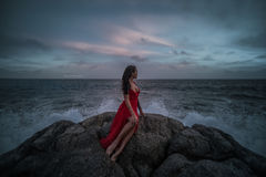 Beautiful seductive woman in red dress enjoying herself on rocks by the sea Royalty Free Stock Photography