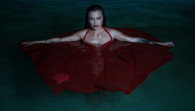 Beautiful seductive woman wearing red dress in outdoor pool at night Royalty Free Stock Photos