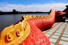 Beautiful Red and Gold colors of Praya Nark or Naga in Thai temple with colorful sky and sun flare effect on sunrise time Royalty Free Stock Photography
