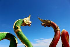 Beautiful Red and Green colors of Two Praya Nark or Naga in Thai temple with colorful sky and sun flare effect on sunrise time Royalty Free Stock Images