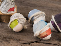 Beautiful selfmade easter eggs. Close up of some selfmade easter eggs taped with newspaper on a wooden table royalty free stock photo