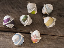 Beautiful selfmade easter eggs. Selfmade beautiful easter eggs sticked with newspaper on a wooden table Royalty Free Stock Photos
